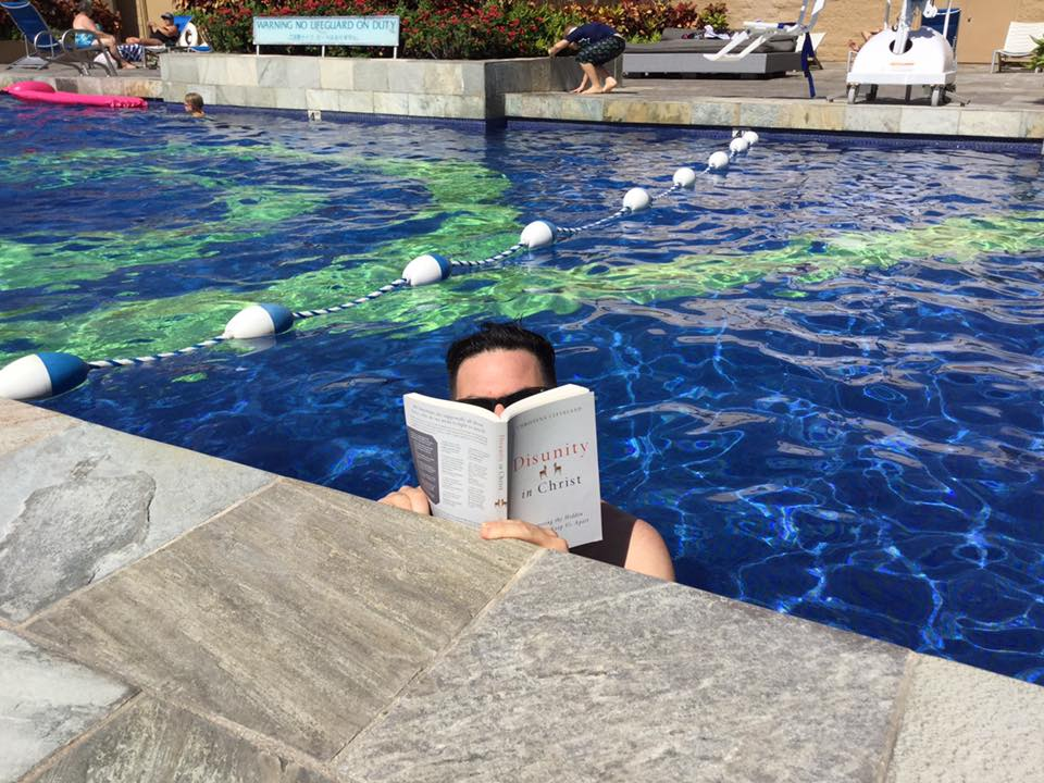 "Monte holding up and reading the book ""Disunity in Christ"" in a swimming pool."