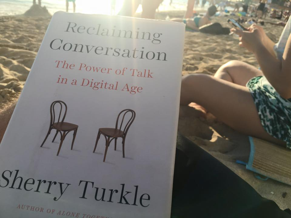 "Monte reading the book ""Reclaiming Conversation"" on Waikiki beach.  The person near him on the beach is on a smart phone."