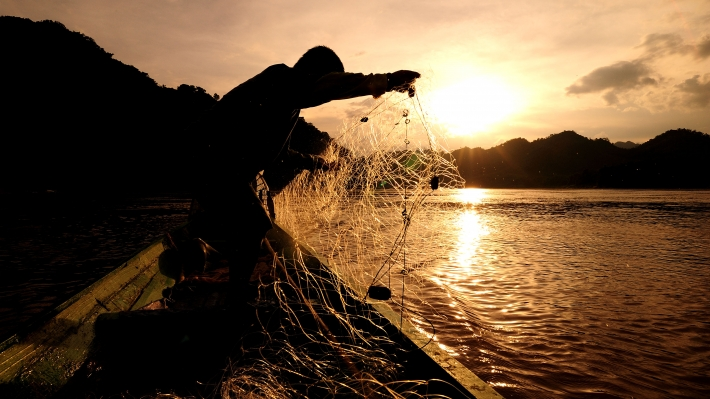 Fisherman throwing net from boat